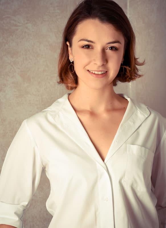 junge Frau vor mellierter Wand Bewerbungsfoto