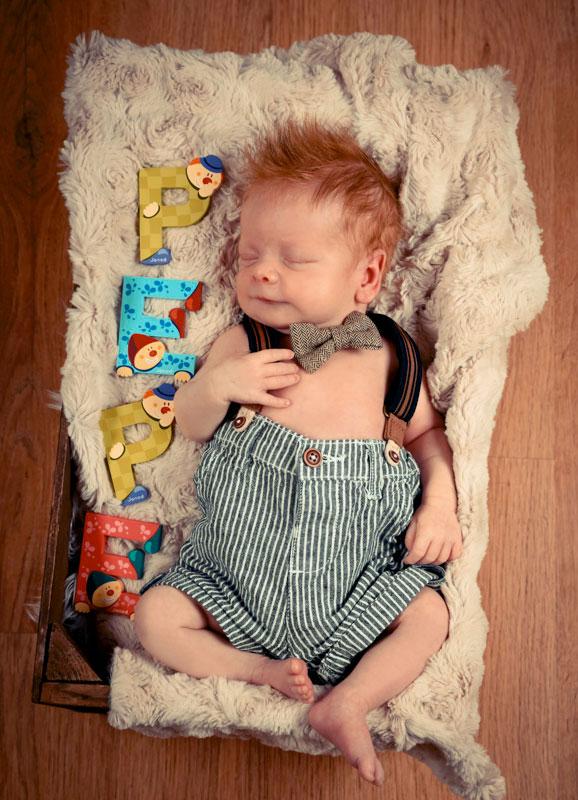 süßes Baby mit vielen Haaren in Kiste